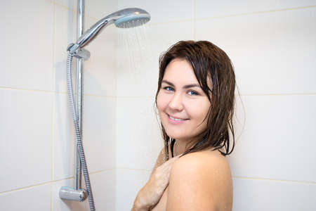 taking shower: portrait of young beautiful woman taking shower