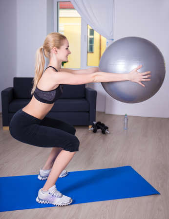 cuclillas: feliz joven mujer delgada en cuclillas con forma de bola en el hogar