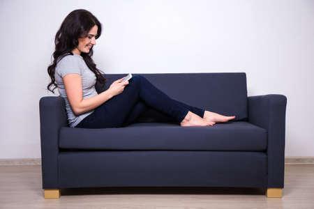 persona sentada: mujer feliz joven que se sienta en el sof� y el uso de tel�fono m�vil
