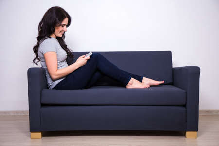 person sitting: young happy woman sitting on sofa and using mobile phone