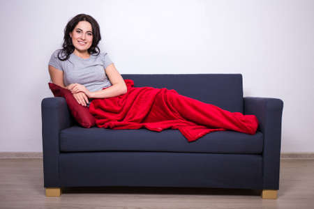 red sofa: happy young woman sitting on sofa wrapped in red blanket