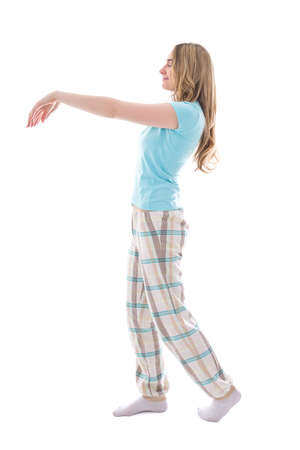 somnambulism: young sleepwalking woman in pajamas isolated on white background