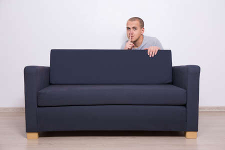 shhh: young handsome man hiding behind a sofa and showing shhh sign