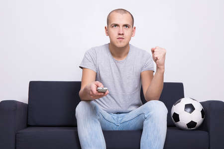 watching television: young man soccer fan with ball watching tv at home