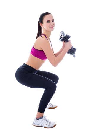 en cuclillas: hermosa mujer delgada en ropa deportiva en cuclillas con pesas aislados sobre fondo blanco Foto de archivo