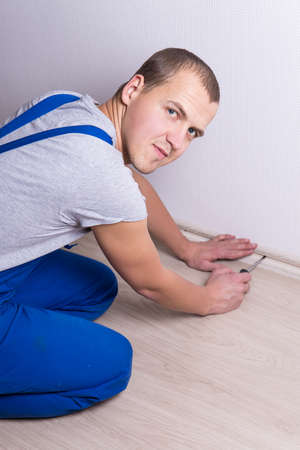 baseboard: young worker in uniform installing new baseboard at home Stock Photo