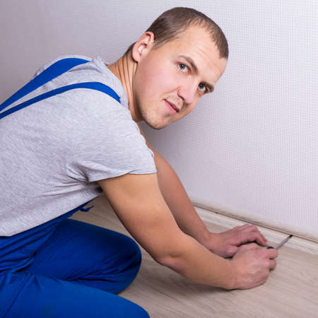 young worker in uniform installing new skirting board at home
