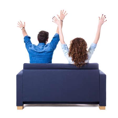 pareja viendo television: Vista posterior de la pareja alegre joven sentado en el sofá aislado en el fondo blanco