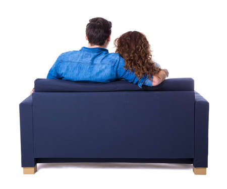 back view of young couple sitting on sofa isolated on white background