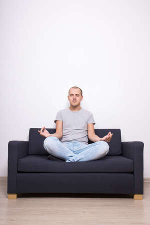 meditation room: meditation concept - tired man sitting on sofa in yoga pose in living room