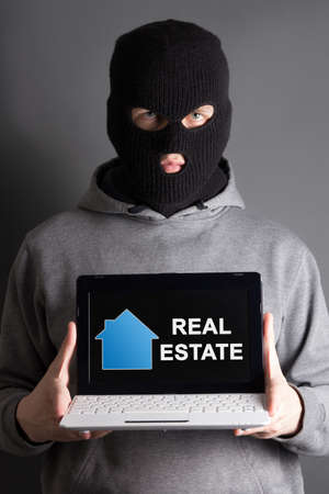 malefactor: burglary and home safety concept -masked man holding computer with real estate site