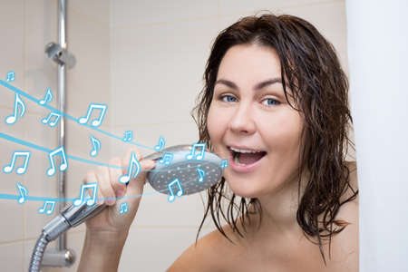 shower head: portrait of funny cheerful woman singing in shower Stock Photo