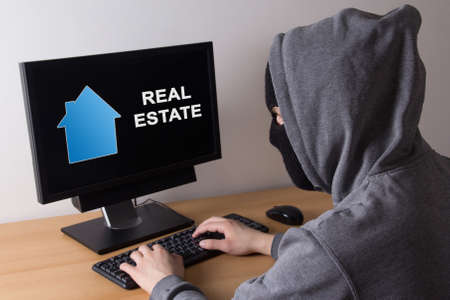 fraudster: criminal and burglary concept - thief in mask searching info about real estate in internet