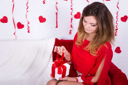 opening gift: young gorgeous woman in red dress opening gift box