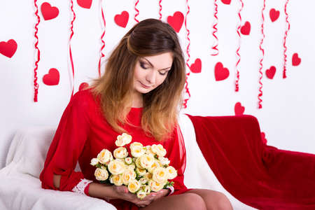 red sofa: gorgeous young woman in red dress sitting on sofa with flowers in decorated room Stock Photo