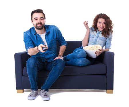 joven hombre feliz y una mujer sentados en el sofá con palomitas y viendo la TV aislado en el fondo blanco Foto de archivo