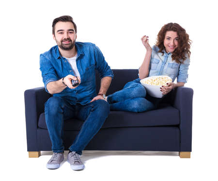 young happy man and woman sitting on sofa with popcorn and watching tv isolated on white background
