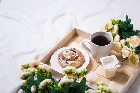 morning concept - breakfast with sweet bun, tea and yoghurt on wooden tray and flowers