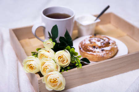 breakfast hotel: wooden tray with continental breakfast and flowers Stock Photo