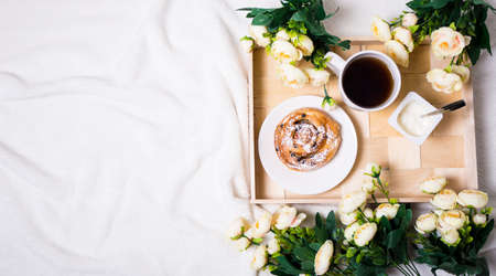 top view of breakfast with sweet bun, tea and yoghurt on wooden tray and flowers