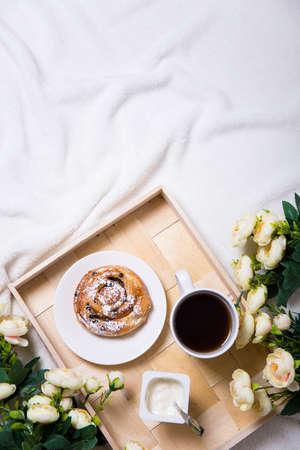 desayuno romantico: buena mañana - el desayuno con pan dulce y el té en bandeja de madera y flores en la cama Foto de archivo