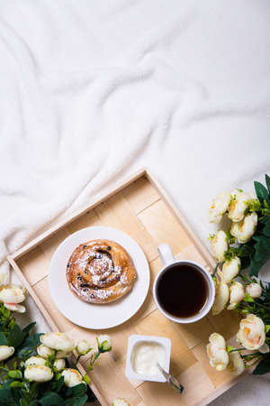 good morning - breakfast with sweet bun and tea on wooden tray and flowers in bed