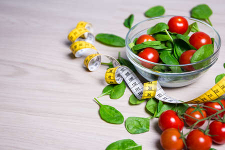 close up food: diet concept - salad with spinach and tomatoes, measure tape and copy space on wooden table  background