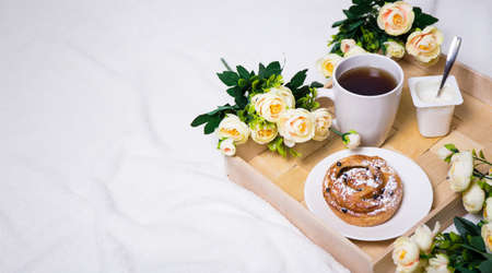 breakfast in bed with bun, tea and yoghurt on wooden tray and flowers