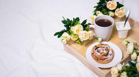 desayuno romantico: desayuno en la cama con el bollo, té y yogur en la bandeja de madera y flores Foto de archivo