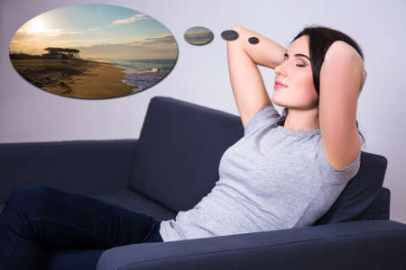 think about: young woman lying on sofa at home and dreaming about summer vacation Stock Photo