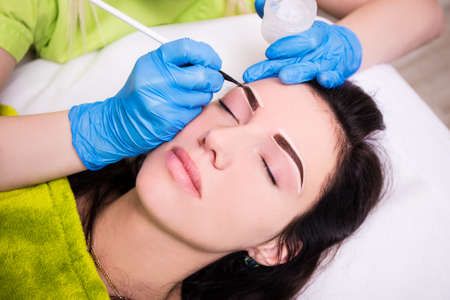 anesthesia: permanent eyebrow make up - beautician applying anesthesia and preparing young woman for procedure