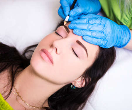 make up applying: permanent eyebrow make up - close up of beautician preparing woman for procedure