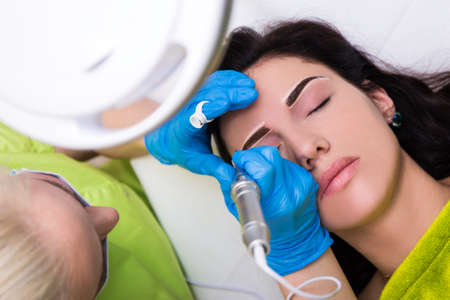 top view of cosmetologist applying permanent make up on female eyebrows