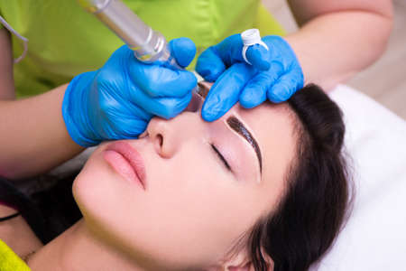 close up of cosmetologist applying permanent make up on female eyebrows