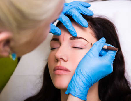 cosmetician: permanent eyebrow make up - close up of cosmetician preparing client for procedure Stock Photo