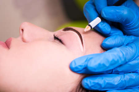 permanent: close up of beautician preparing young beautiful woman for permanent eyebrow make up procedure Stock Photo