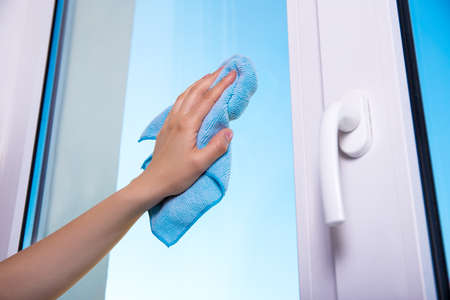 dry cleaners: close up of womans hand with special rag cleaning window