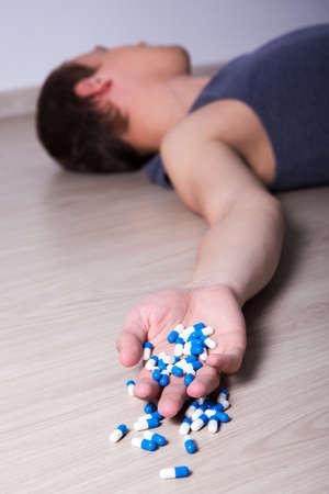 sobredosis: joven tendido en el suelo en casa después de una sobredosis de píldoras