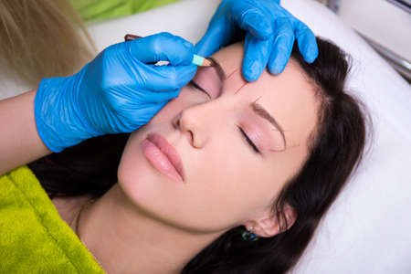 permanent: close up of cosmetician preparing young woman for permanent eyebrow make up