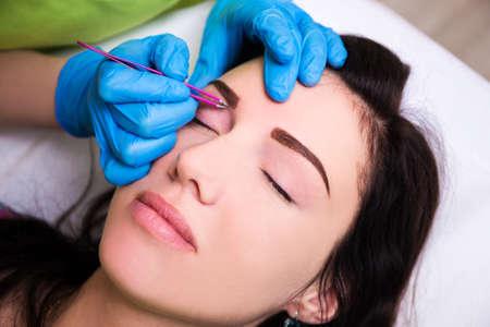 tweezing eyebrow: close up of woman getting tweezing eyebrow by beautician