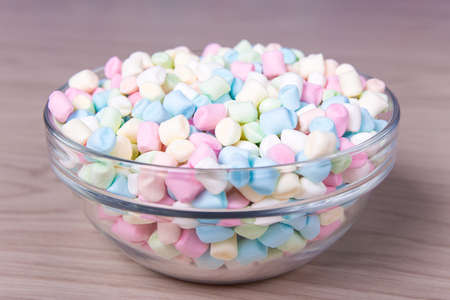 soft colors: colorful mini marshmallows in glass bowl on wooden table