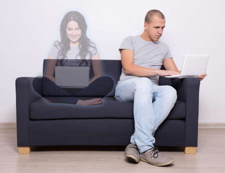 online dating concept - handsome man sitting on sofa with laptop and chatting with imaginary girl Stock Photo