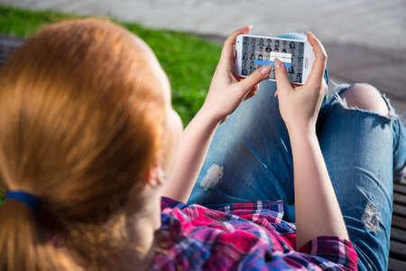 mobile internet concept - modern smart phone in teenage girl hands photo