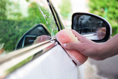 handle car wash concept - male hand with soap sponge