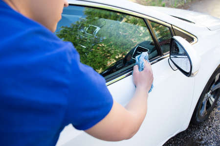 back view of young man cleaning car with blue microfiber cloth