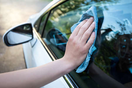 mâle fenêtre de la voiture de nettoyage à la main avec un chiffon en microfibres bleu