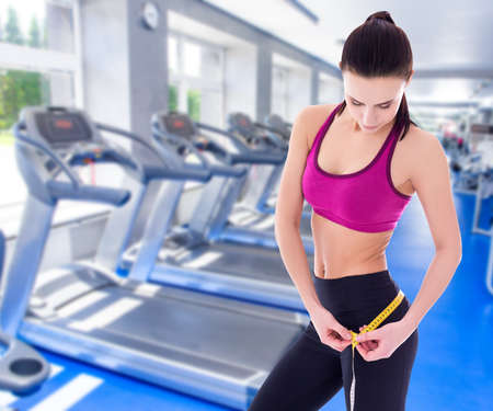 weightloss: weightloss and diet concept - beautiful slim sporty woman with measure tape in modern gym Stock Photo