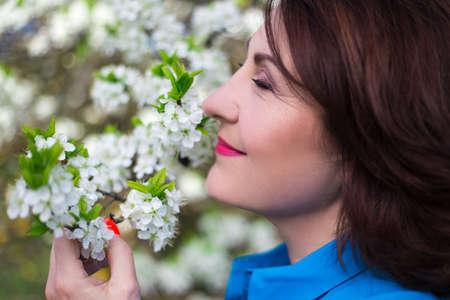 cerca retrato de mujer de mediana edad feliz oliendo rama de un árbol de cerezo en el jardín de primavera