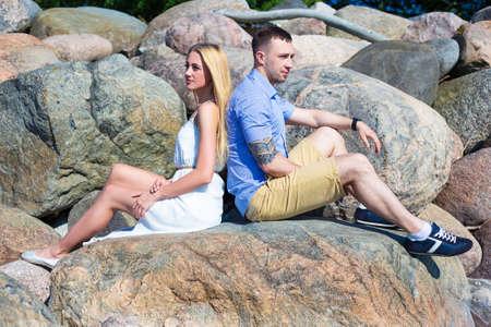romantic portrait of happy couple in love sitting on big stone Stock Photo