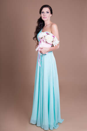 full length portrait of young beautiful woman holding box with flowers